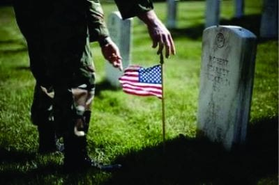 soldier placing grave stone flag